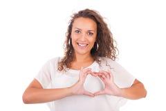 Schöne junge Frau, die ein Herz mit den Händen macht stockfotografie