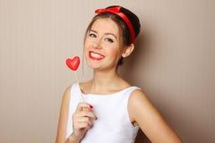 Schöne junge Frau, die ein rotes Inneres anhält Lizenzfreie Stockbilder