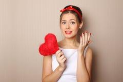 Schöne junge Frau, die ein rotes Inneres anhält Stockfotografie
