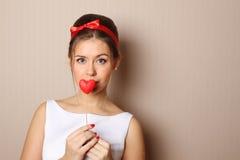 Schöne junge Frau, die ein rotes Inneres anhält Lizenzfreie Stockfotos