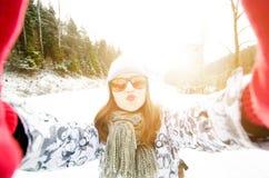 Schöne junge Frau, die ein selfie in der Winternatur nimmt Hübsche Frau, die ein Foto in einer Natur macht Weiße Schneeflocken au stockfotos