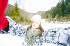 Schöne junge Frau, die ein selfie in der Winternatur nimmt Hübsche Frau, die ein Foto in einer Natur macht Weiße Schneeflocken au lizenzfreie stockfotografie