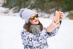 Schöne junge Frau, die ein selfie in der Winternatur nimmt Hübsche Frau, die ein Foto in einer Natur macht Weiße Schneeflocken au stockfotografie