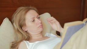 Schöne junge Frau, die ein trauriges Buch im Bett liest stock video footage