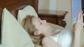 Schöne junge Frau, die ein trauriges Buch im Bett liest stock footage