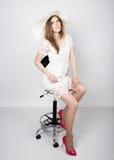 Schöne junge Frau, die ein weißes Kleid und hohe Absätze, sitzend auf einem Stuhl trägt Stockbilder