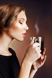Schöne junge Frau, die eine Kaffeetasse mit geschlossenen Augen hält Stockfotografie