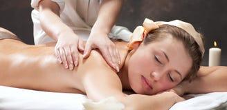 Schöne junge Frau, die eine Massage erhält stockbilder