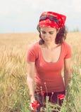 Schöne junge Frau, die eine Mohnblume auswählt Stockbilder
