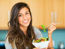 Schöne junge Frau, die eine Schüssel gesunden organischen Salat isst Stockfotos