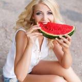 Schöne junge Frau, die eine Scheibe der reifen Wassermelone hält Lizenzfreie Stockfotos