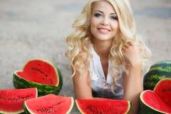 Schöne junge Frau, die eine Scheibe der reifen Wassermelone hält Stockbild