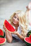 Schöne junge Frau, die eine Scheibe der reifen Wassermelone hält Lizenzfreie Stockbilder
