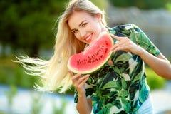 Schöne junge Frau, die eine Scheibe der Wassermelone zeigt Sie ist kaukasisch Sommer- und Lebensstilkonzepte stockfotografie