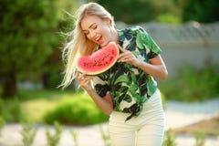 Schöne junge Frau, die eine Scheibe der Wassermelone zeigt Sie ist kaukasisch Sommer- und Lebensstilkonzepte stockfoto