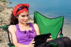 Schöne junge Frau, die eine Tablette in den Ferien verwendet Lizenzfreie Stockbilder