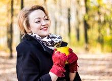Schöne junge Frau, die eine Tasse Tee im Herbstpark lächelt und hält Stockfotos