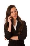 Schöne junge Frau, die an einem Handy spricht Lizenzfreie Stockbilder