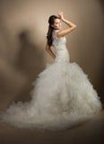 Schöne junge Frau, die in einem Hochzeitskleid aufwirft lizenzfreie stockfotos