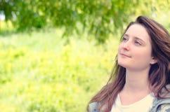 Schöne junge Frau, die in einem Park träumt lizenzfreie stockfotos
