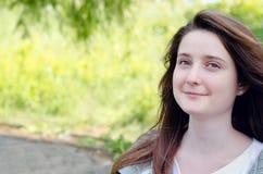 Schöne junge Frau, die in einem Park träumt stockbild