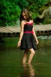 Schöne junge Frau, die in einem Seewald sich entspannt Stockfoto
