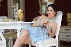 Schöne junge Frau, die in einem Stuhl mit einem Cup oj-Tee in weiter entwickeltem Innenraum sitzt Lizenzfreies Stockfoto