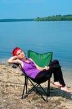 Schöne junge Frau, die in einem Stuhl nahe dem See schläft Stockfotos