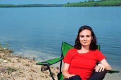 Schöne junge Frau, die in einem Stuhl nahe dem See sich entspannt Stockfotos