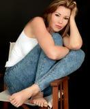 Schöne junge Frau, die in einem Stuhl sitzt Lizenzfreie Stockbilder