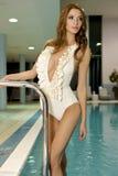 Schöne junge Frau, die in einem Swimmingpool steht stockbilder