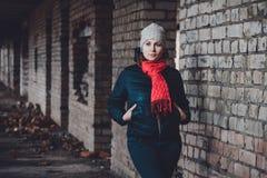 Schöne junge Frau, die in einem zerstörten Gebäude im kalten Ertrinken steht stockfoto