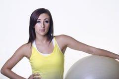 Schöne junge Frau, die einen Übungsball hält Stockfotos