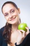Schöne junge Frau, die einen Apfel anhält Stockfotos