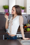 Junge Frau, die einen Apfel isst Stockbild