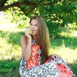 Schöne junge Frau, die einen Apfel isst Stockbilder