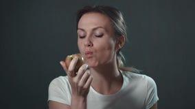 Schöne junge Frau, die einen Apfel isst Getrennt über Weiß Lokalisiertes Schwarzes Porträt stock footage
