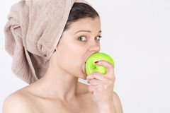 Schöne junge Frau, die einen Apfel schlägt. Stockbild