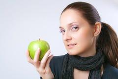 Schöne junge Frau, die einen Apfel zeigt Lizenzfreie Stockfotos