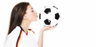 Schöne junge Frau, die einen Fußball küßt Stockfotografie