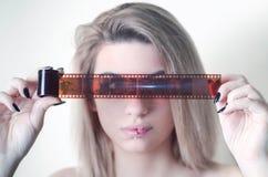Schöne junge Frau, die einen Kamerafilm hält Lizenzfreie Stockfotografie