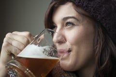 Schöne junge Frau in gestricktem Schal-und Hut-Getränk-Bier lizenzfreies stockbild