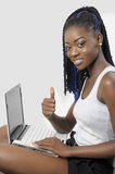 Schöne junge Frau, die einen Laptop sich zeigt Daumen verwendet Stockbild
