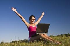 Schöne junge Frau, die einen Laptop verwendet Stockbilder