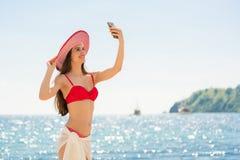 Schöne junge Frau, die einen modischen gestreiften Hut bei der Aufstellung trägt Stockfotos