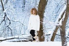 Schöne junge Frau, die in einen schneebedeckten Park geht Stockbilder