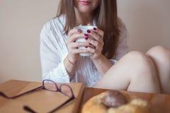 Schöne junge Frau, die einen Tasse Kaffee in ihren Händen hält Stockbild