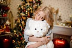Schöne junge Frau, die einen Teddybären, Weihnachtsbaum im Hintergrund umarmt Lizenzfreie Stockfotos