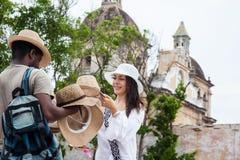 Schöne junge Frau, die einen traditionellen kolumbianischen Hut von einem Straßenhändler aufkauft stockfoto