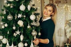 Schöne, junge Frau, die einen Weihnachtsbaum verziert Lizenzfreie Stockfotografie
